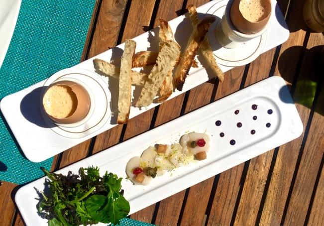 Tapas de Carpaccio de Saint-Jacques marinée aux agrumes et Oeuf de ferme mi-cuit, crème légère aux oursins et ses mouillettes