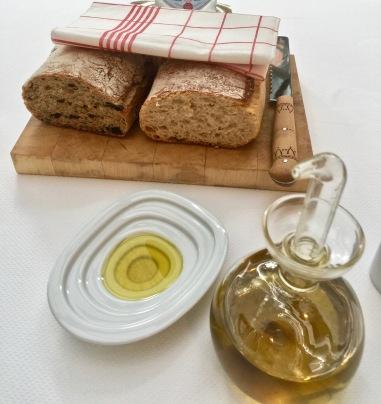 Deux sortes de pain maison, levain et olives, posés sur une planche et à découper soi-même ©lepetitlugourmand
